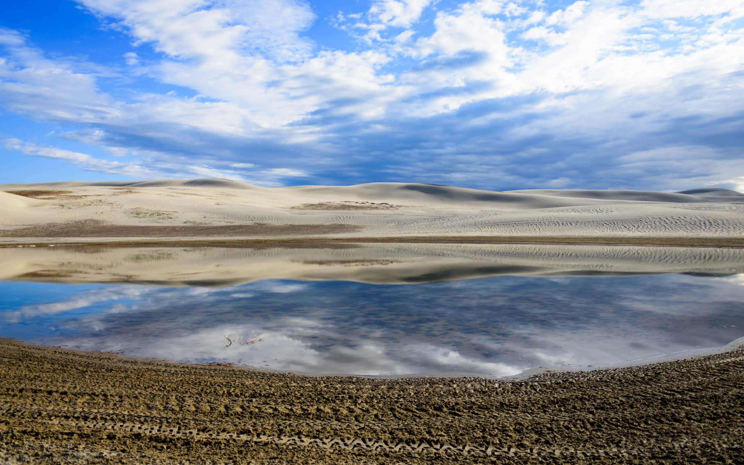 Landscape of sand dunes reflected in a pond.