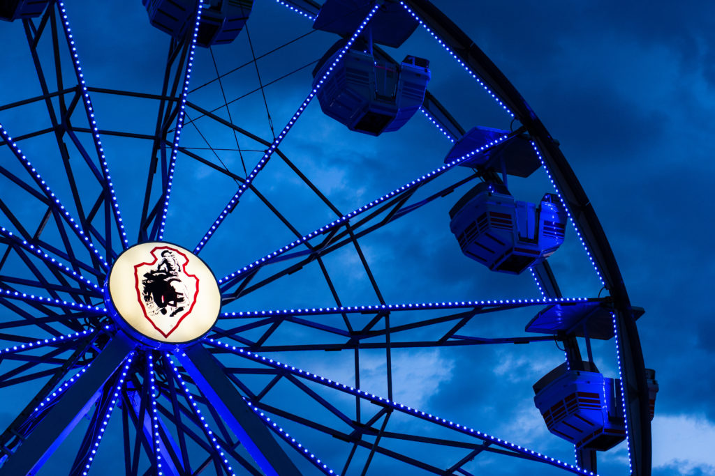A photo of the Cheyenne Frontier Days ferris wheel with stormy clouds in the background.